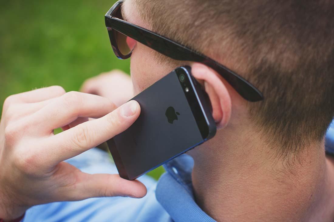 Chico escuchando un mensaje de voz de WhatsApp en su iPhone